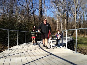 concrete boardwalk family and dog walker