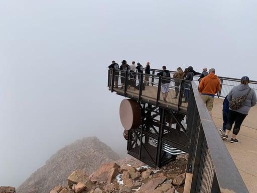 Pikes Peak Summit complex visitors walk on PermaTrak boardwalk hanging over mountain range