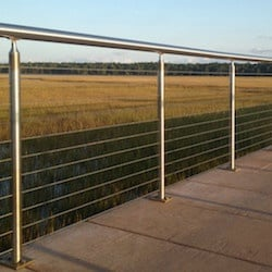 A stainless steel railing with cable strands